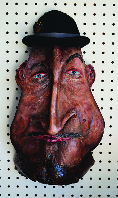 "**Super Silly Us ** Affectionately known as the man in the bowler hat, this mask reminds me of a upper crust fellow looking down his long nose at the lesser beings around him.  Mask size: 17"" high by  X 9 ½"" wide"
